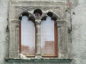la caratteristica finestra bifora con giglio in ferro battuto di piazza Umberto I